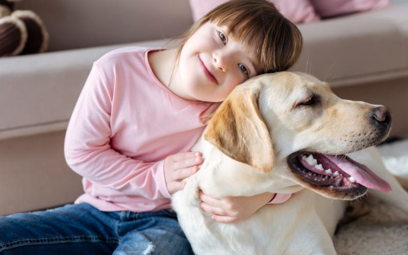 niña con síndrome de Down sonriendo a la cámara y abrazando un perro labrador