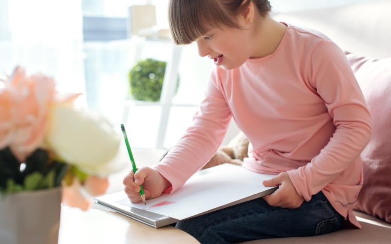 niña con síndrome de down con un agarre funcional de lápiz escribiendo